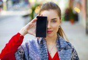 Young woman covers her face screen smartphone on a background of the city